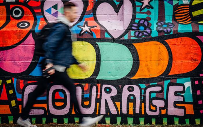 Man die wandelt langs een muur met het woord courage op