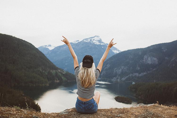 Vrouw die op een klif zit met haar handen in de lucht
